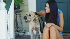 Mixed race woman sitting on porch taking pictures with dog Stock Footage