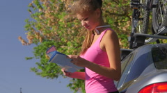 Young fit woman driver stand near car and look on map for directions Stock Footage