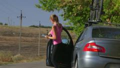 Young woman driver traveling by car with bicycle on roof Stock Footage