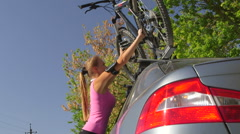 Woman cyclist fixing bicycle on roof of car after workout Stock Footage
