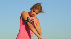 Fitness young woman touching phone screen in arm sport band before exercise Stock Footage