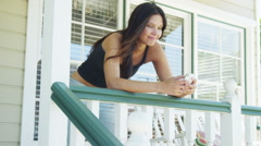 Hispanic woman leaning on rail texting Stock Footage