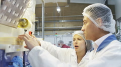 Two workers in pharmaceutical manufacturing facility - stock footage