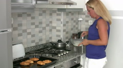 Woman cooking  in her kitchen at home Stock Footage