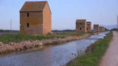 Unusual square adobe huts along an irrigation canal near Albufera, Spain. Stock Footage