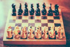 Ancient wooden chess standing on chessboard Stock Photos
