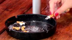 Woman puts smoldering cigarette in ashtray. - stock footage