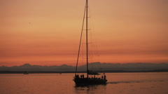 Yacht  sailing in Puget sound in evening with mountain range in background Stock Footage