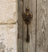 Old iron handle on wooden door next to wall Stock Photos
