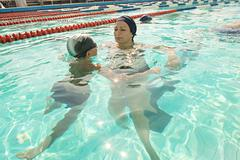 Mom and her son in swimming pool. Mother giving son a swimming lesson in pool Kuvituskuvat