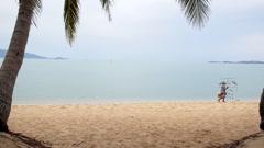 Thai Man Selling Souvenirs at Beach in Koh Samui, Thailand. Stock Footage