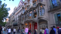 Pedestrians walk in front of a Gaudi designed building in Barcelona, Spain. Stock Footage