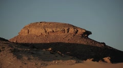 Time-lapse of sunset over a rocky outcrop in the Sahara Desert, Egypt - stock footage