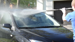 Worker man wash car windscreen with strong pressure water jet Stock Footage