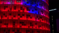 Stock Video Footage of Remarkable blue and red skyscraper at night in Barcelona, Spain.
