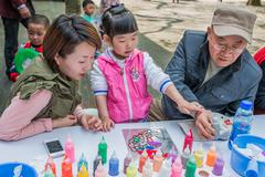 three generation family sketching leisure in fuxing park shanghai china - stock photo