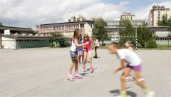 Children playing hopscotch. Young girls riding roller skates. Kids game. Teens. - stock footage