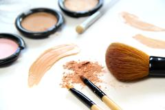 broken powder, foundation and brushes - stock photo
