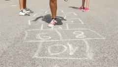 Children playing hopscotch on the asphalt in school yard. Jumping. Legs close up Stock Footage
