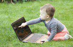 cute baby girl using a laptop - stock photo