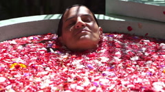 Woman diving in the bath full of flowers, slow motion shot Stock Footage