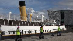 Segway tour passes titanic belfast visitor centre, northern ireland Stock Footage