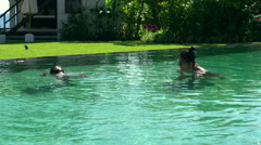 Mother and her son having fun while diving in the swimming pool Stock Footage
