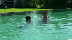 Mother teaching her son how to dive in the swimming pool Stock Footage