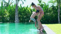Mother jumping with her son into swimming pool and having fun Stock Footage
