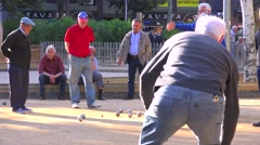 Retired men play a game of bowls in Barcelona, Spain. - stock footage