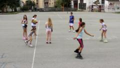 Young girls riding with roller skates. Children playing with ball. Race. Kids. - stock footage