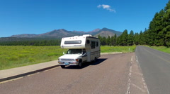 Mini RV On Side Of Road In Forest With Meadow And Mountains Stock Footage