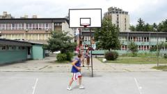 Girls sitting on structure of basket. Boy playing basketball on school ground. Stock Footage