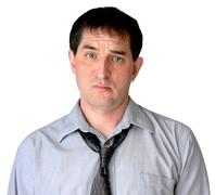 Man in grey dress shirt and loosened tie looking unimpressed Stock Photos