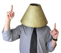Man in grey dress shirt and tie wearing lampshade on head and acting jovially - stock photo