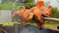 Traditional barbecue grill piglet pig on a metal roaster skewer Stock Footage