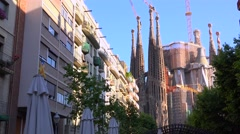 The Sagrada Familia cathedral by Gaudi amongst apartments and buildings in Stock Footage