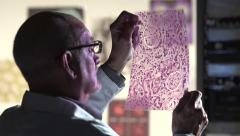 Male Scientist looking at purple transparency - dolly Stock Footage