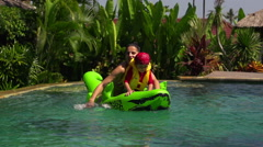 Mother and son falling out from toy to the pool, slow motion shot Stock Footage