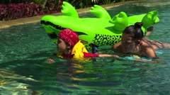 Boy pulling his mother on toy in the swimming pool, slow motion shot at 240fps Stock Footage