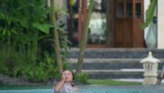 Boy jumping to the pool and diving, slow motion shot Stock Footage