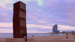 An odd sculpture stands on a beach in Barcelona, Spain. - stock footage