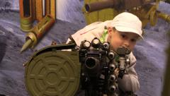 Little boy sees Automatic Grenade Launcher AGS-17 on exhibition OBORONEXPO 2014 Stock Footage