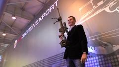 Civil man posing with a heavy sniper rifle on the stand ROSOBORONEXPORT. Stock Footage