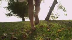 Low angle of womans legs walking in slow motion on grass bare foot Stock Footage