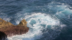 Ocean currents and waves churning around rocky point - time lapse - stock footage