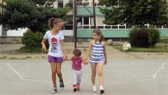 Two young girls raising little child and passing by the camera on school court. Stock Footage