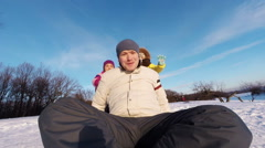 Portrait of man riding on a sled down the hills. Wife and daughter accompany  Stock Footage