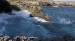 Waves washing up against volcanic rock cliff face Stock Footage