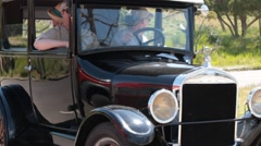 Black Ford Model T Horseless Carriage Reverses Out into Modern Traffic Stock Footage